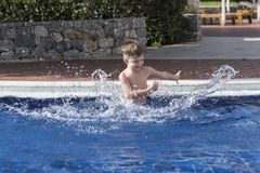 Boy plaiyng in swimming pool stock image