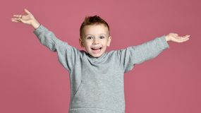 Young boy kid jumping in grey hoodie with hands spread up laughing smiling on pink stock images
