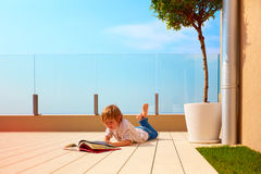 Young boy, kid reading book on rooftop terrace, while lying down on decking. Sunny day Royalty Free Stock Photography