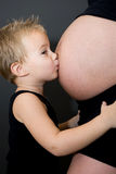 Young boy kisses the belly Royalty Free Stock Photo