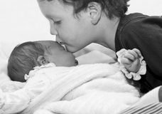 Young boy kissing baby sister Stock Photo