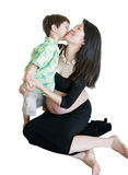 Young Boy kissing pregnant mom. Mixed asian-caucasian 3 years old kissing pregnant mom isolated on white background Stock Photos