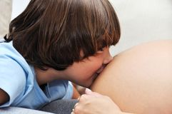 Young boy kissing pregnant woman Stock Photography