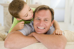 Young boy kissing smiling man in living room Stock Photography