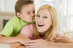 Young boy kissing smiling woman in living room Stock Images