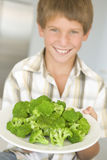 Young boy in kitchen eating broccoli smiling Royalty Free Stock Photo