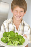 Young boy in kitchen eating broccoli smiling Stock Photography