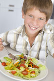 Young boy in kitchen eating salad smiling Stock Photo