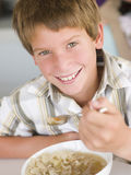 Young boy in kitchen eating soup and smiling Stock Image