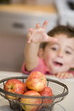Young boy in kitchen getting apple off counter stock photography