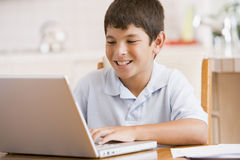 Young boy in kitchen with laptop and paperwork Stock Photography
