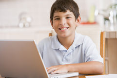 Young boy in kitchen with laptop and paperwork Stock Images