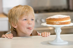 Young boy in kitchen looking at cake on counter Royalty Free Stock Photos
