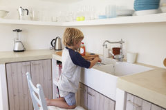 Young boy kneeling on a chair to wash dishes, full length Stock Photography