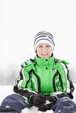 Young boy kneeling in the snow making snowballs Royalty Free Stock Photography