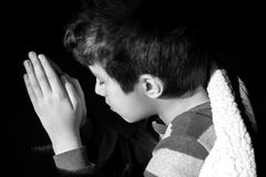 Young boy kneeling to pray at bedtime, eyes closed, picture of i Stock Images