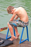 Young Boy on a Ladder. A young boy sitting on a ladder at the water thinking. He has his life jacket and ski at his feet. Maybe he's thinking about the end of royalty free stock photo