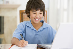Young boy with laptop doing homework Royalty Free Stock Photography