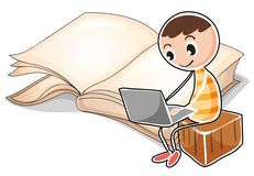 A young boy with a laptop near the big book Stock Image