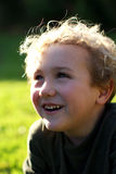 A young boy laughing. With grass in the background Royalty Free Stock Photo