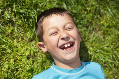 Young boy laughing while lying on the grass Stock Photos