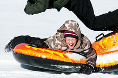 Young boy laughing on a snow tube Royalty Free Stock Photography