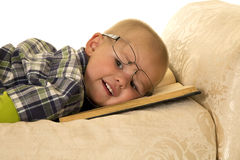 Young boy laying on a a book with glasses on Stock Photography