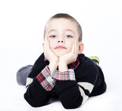 Young boy laying down in studio. Young boy laying on stomach with chin resting in hands in studio isolated on white Stock Photos