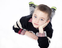 Young boy laying down in studio. Young boy laying on stomach with chin resting in hand in studio isolated on white Stock Images