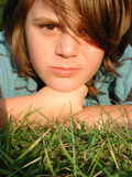 Young boy laying in grass. Close up of cute boy model looking into camera stock photo