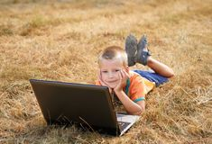 Young boy laying on ground with laptop Royalty Free Stock Photo