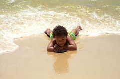 Young Boy Laying On Sand Stock Photography