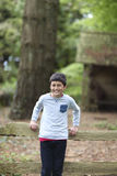 Young boy leaning against fence in park Stock Photo