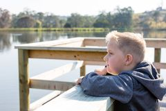 Young boy leaning on a jetty overlooking a lake looking sad stock photo