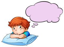 A young boy leaning over the pillow with an empty callout stock illustration