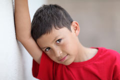 Young boy leans against wall Royalty Free Stock Images