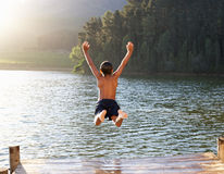 Young boy leaping into lake. Young boy leaping into beautiful lake off jetty royalty free stock images