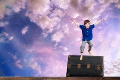 Young Boy Leaps Over an Old Steamer Trunk in Front of a Colorful. Composite piece of a young boy leaping or jumping over an old steamer trunk in front of a Stock Photo
