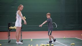 Young boy learning practicing in playing tennis. He hitting the ball. With racquet. Female coach throwing the ball to him stock video footage