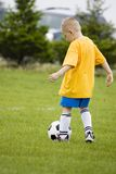 Young boy learning soccer. Here a young boy is learning how to play soccer. He is getting ready to kick the ball to his teammate down the field Royalty Free Stock Photography