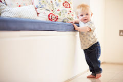 Young Boy Learning To Walk By Holding Onto Furniture Royalty Free Stock Photography