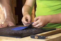 Young Boy learning to work with leather. Young boy being taught by a male adult how to make a blue leather purse Stock Image