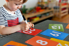 Young boy learning to write numbers on colorful cards with a focus on his hand and his pen Stock Photo