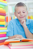Young boy learns from books Royalty Free Stock Images