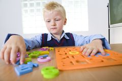 Young boy with letters jigsaw Royalty Free Stock Photo