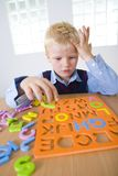 Young boy with letters jigsaw Royalty Free Stock Image