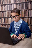 Young boy in the library with glasses working on laptop Royalty Free Stock Image