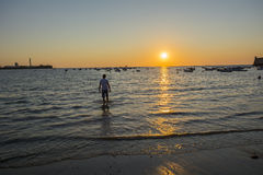 Young boy licking their feet on the beach at sunset Stock Photo