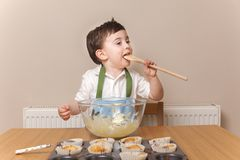Young boy licking wooden spoon Stock Photography