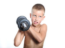 Young boy lifting a very heavy dumbbell Royalty Free Stock Images
